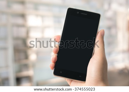 A man holding modern smart phone with blank screen in hand. Closeup shot. Concept for business online - stock photo