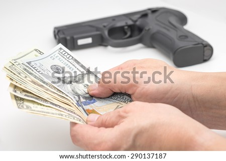 A man holding US dollar banknotes with black gun on white background - stock photo