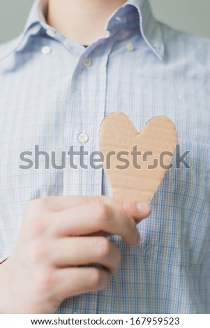 A man holds a heart in his hand - stock photo