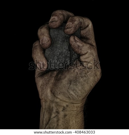 A man holds a lump of coal in a clenched fist. - stock photo
