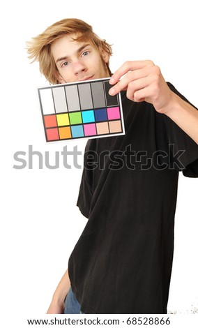 A man holds up an 18 % gray white balance card with test colors on it to calibrate the colors perfectly in post production. - stock photo