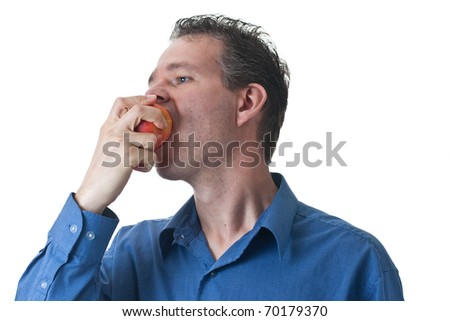 A man in a blue dress shirt, biting into an apple, isolated on white. - stock photo
