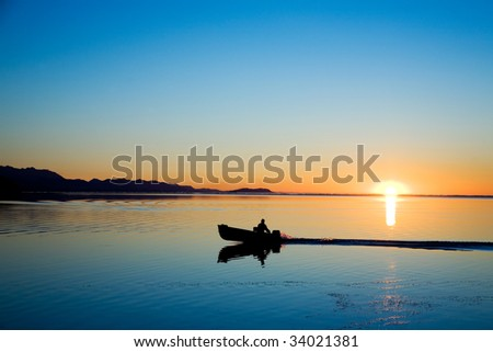 A man in a boat at Cline Spit in Sequim Washington. - stock photo