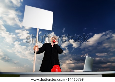 A man in a business suit is at a desk outside holding a sign with space for copy or text while talking over a red telephone. - stock photo