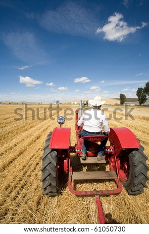 A man in a cowboy hat drives a tractor in a field. - stock photo