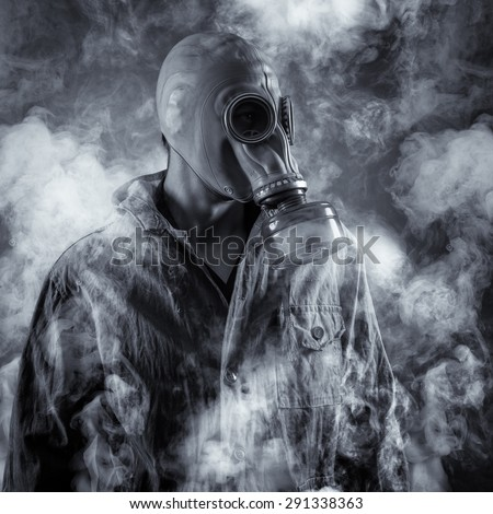 A man in a gas mask shrouded in smoke - stock photo