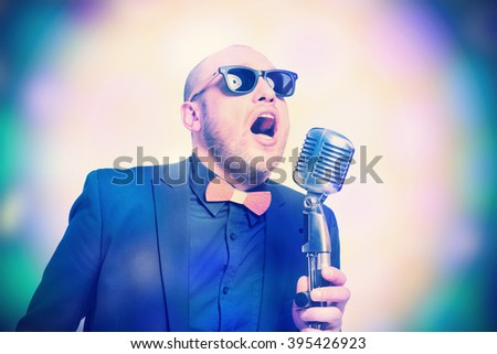 A man in a gray jacket, bow tie and sunglasses with a microphone in hand, singing on the bright abstract background. Toned - stock photo