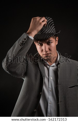 a man in a grey hat on black background - stock photo