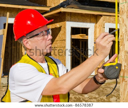 A man in a hard hat standing in front of an house over blue sky with white clouds at sunny day holding a measure tape in his hand. - stock photo