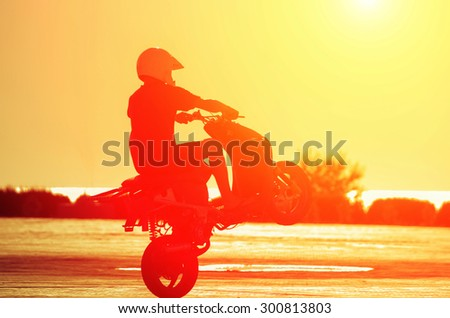 A man in a helmet on a moped shows stunts at sunset. Natural composition - stock photo