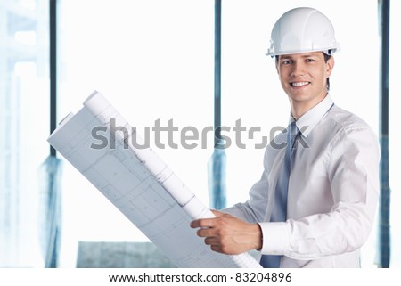A man in a helmet with a plan for construction - stock photo