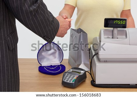 A man in a shop buying a necklace and handing the assistant his credit card to pay. - stock photo