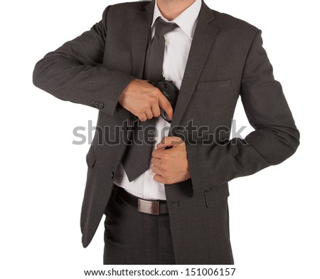 A man in a suit grabbing a gun out his jacket - stock photo