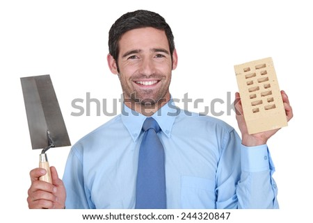 A man in a suit holding a brick and a trowel. - stock photo