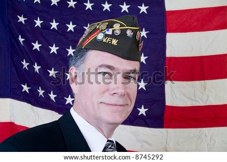 A man in a veteran of foreign wars cap standing in front of a forty-eight star US flag. - stock photo