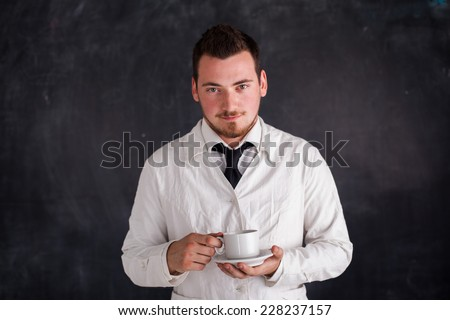 a man in a white gown drinks from a cup - stock photo