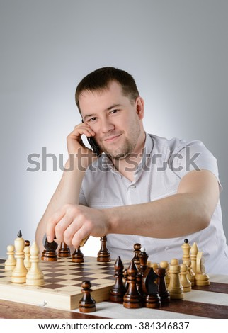 A man in a white shirt and thinks with the phone over a game of chess - stock photo