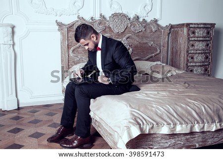 A man in brand-new suit touches his tablet in leather pouch and looks something intently in his gadget - stock photo
