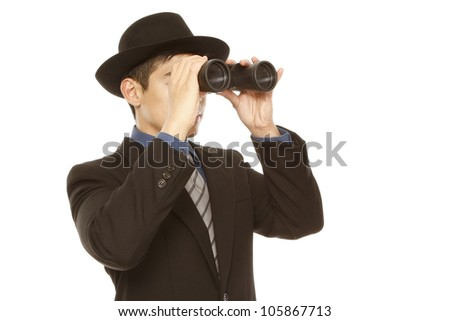 A man in business attire and hat using binoculars - stock photo
