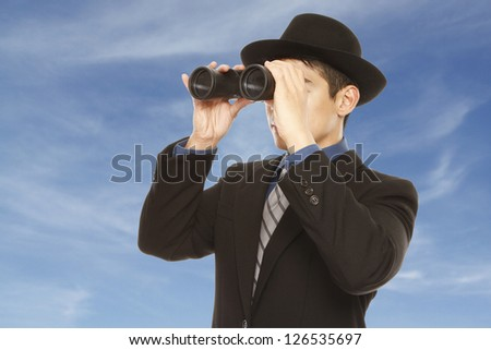 A man in business attire and hat using binoculars (against a dramatic sky background) - stock photo