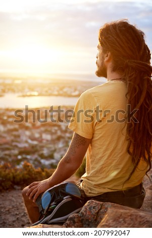 A man in dreadlocks on a mountain looking at the view - stock photo