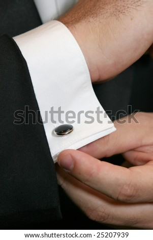 A man in formal attire adjusts his cuff links. - stock photo