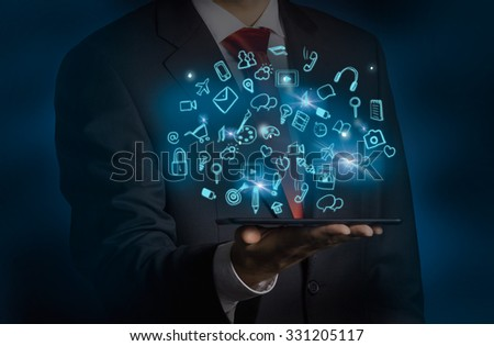 A man in formal suit is holding a tablet with flying out hologram social media icons. Dark background. - stock photo