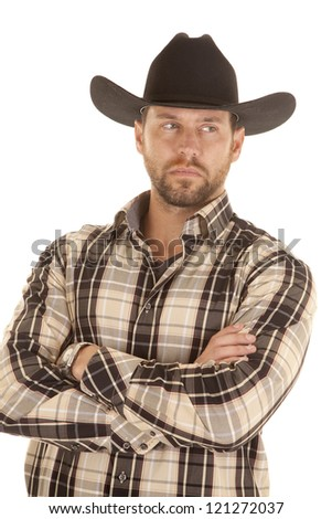 A man in his plaid shirt and black western hat with a serious expression on his face. - stock photo