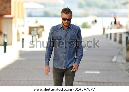 A man in his 20s, wearing a jeans shirt and jeans with dark sunglasses, talking a walk in the city on a sunny summer day. - stock photo