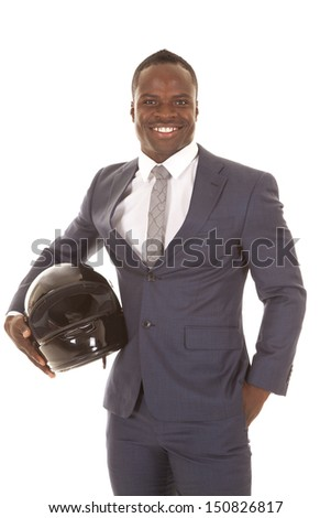 A man in his suit holding on to a helmet with a smile on his face. - stock photo
