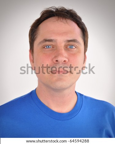 A man in his thirties is staring into the camera and looks calm and kind yet serious. He is wearing a blue t-shirt and is casual. - stock photo