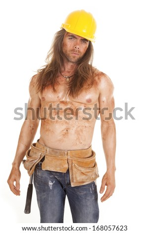 A man in his tool belt and hard hat with dirt and mud all over his body. - stock photo