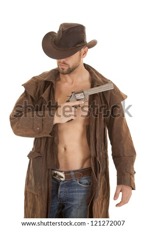 A man in his western duster and hat holding on to a pistol - stock photo