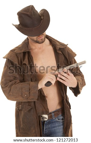 A man in his western duster holding on to his weapon. - stock photo