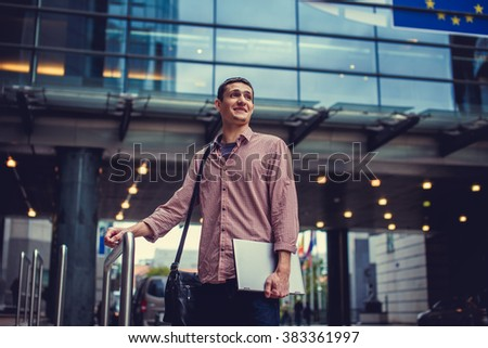 A man in red shirt holds laptop on the street. - stock photo