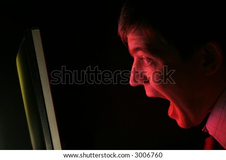 A man in shirt and tie screams at a red computer monitor. Anger? Frustration? Fear? - stock photo