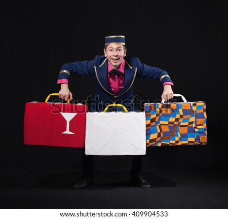 A man in uniform concierge is catches  balance with luggage  - stock photo