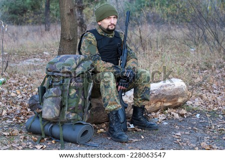 A man in uniform is resting in the forest - stock photo