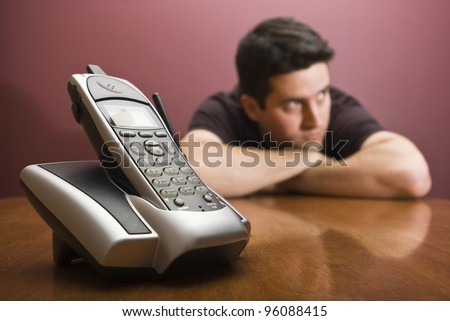 A man is bored waiting for the phone to ring - stock photo