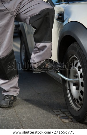 A man is changing a car tire with the help of his  feet - stock photo
