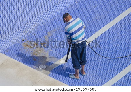 A man is cleaning the pool ground with a pressure pump - stock photo