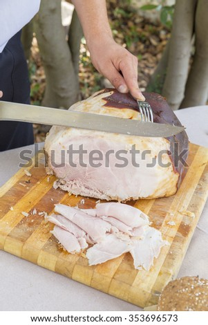 a man is cutting a pork ham on a wooden cutting board - stock photo