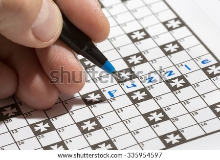 A man is doing crossword puzzle. The man is holding a pencil in his hand and there is a word 'puzzle' already written in the crossword. Crossword puzzles are excellent training for brains. - stock photo