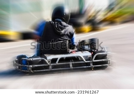 A man is driving Go-kart with speed in the park on karting track - behind view. - stock photo