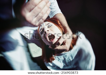 A man is forcing a woman to take pills holding her head. - stock photo