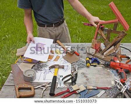 A man is frustrated and angry at building a bad birdhouse. - stock photo