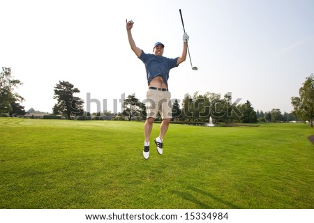 A man is jumping up and down on a golf course.  He is holding a golf club and smiling at the camera.  Horizontally framed shot. - stock photo