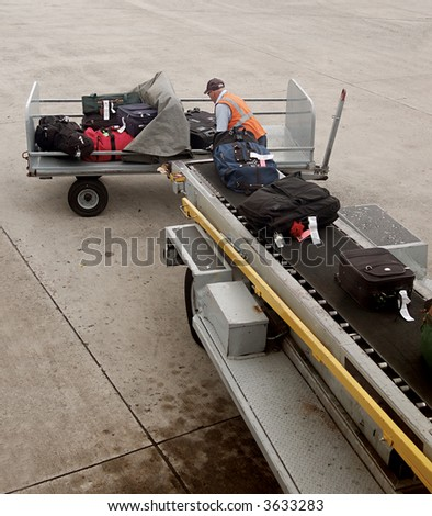 A man is loading luggage onto airplane - stock photo