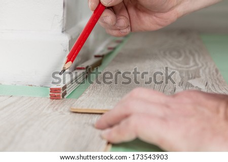 A Man is measuring the right distance to the wall before sawing the wood. - stock photo
