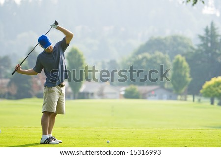 A man is playing golf on a golf course.  He is holding his golf club over his shoulders and looking away from the camera.  Horizontally framed shot. - stock photo